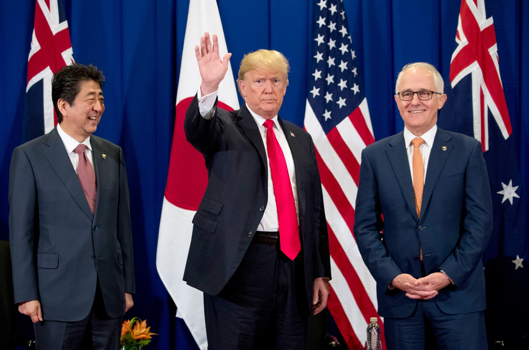 President Trump (center) waving, with Japanese Prime Minister Shinzō Abe, left, and Australian Prime Minister Malcolm Turnbull standing beside him (© AP Images)