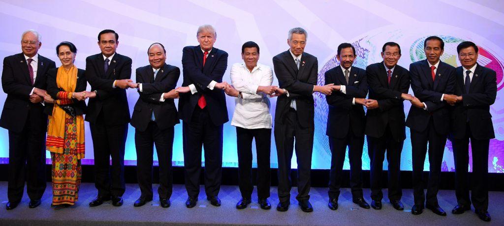 단체 사진 포즈를 취하면서 지도자들이 손을 잡고 있다 (© AP Images)