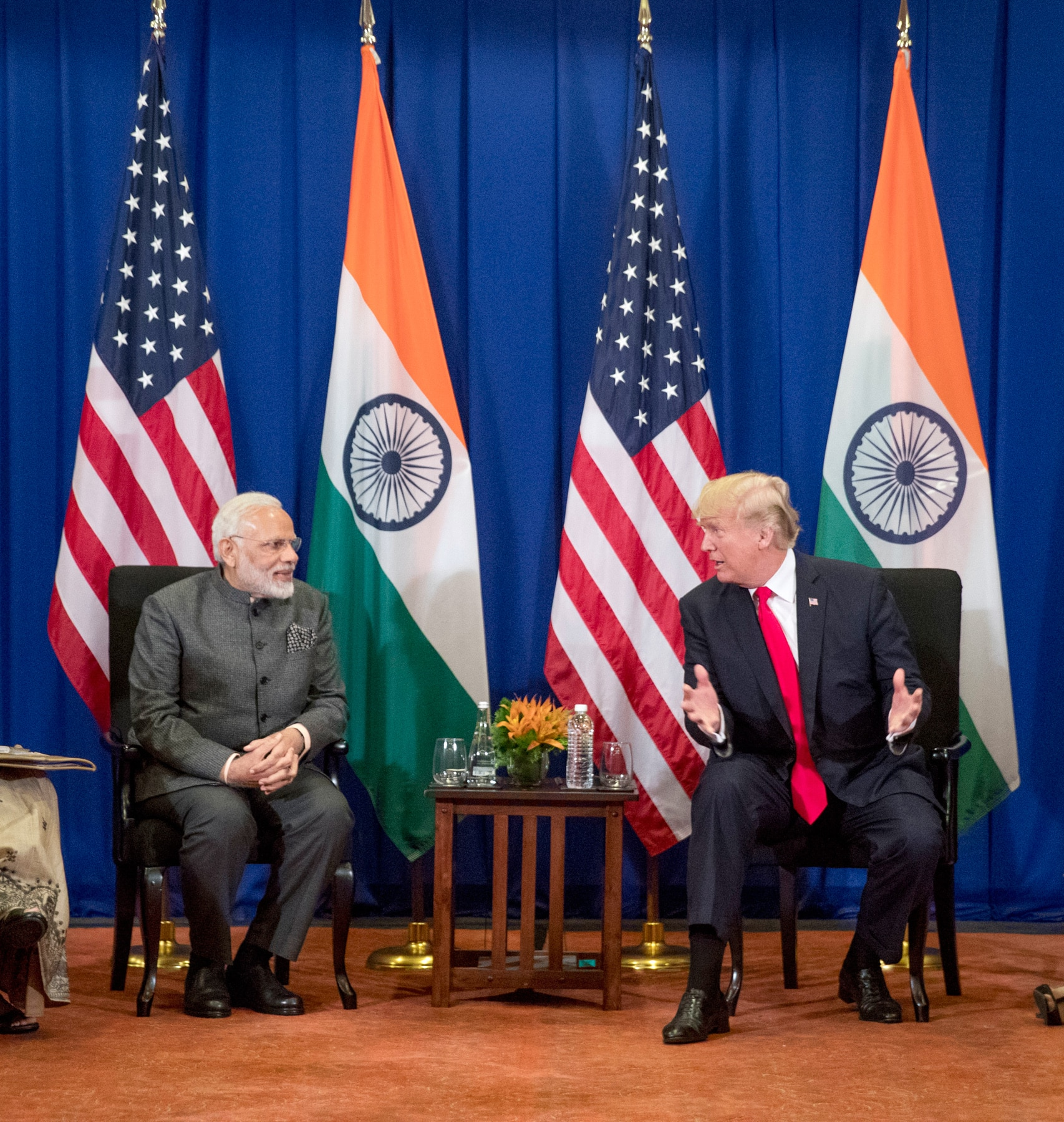President Donald Trump, right, and Indian Prime Minister Narendra Modi speaking to each other while seated (© AP Images)