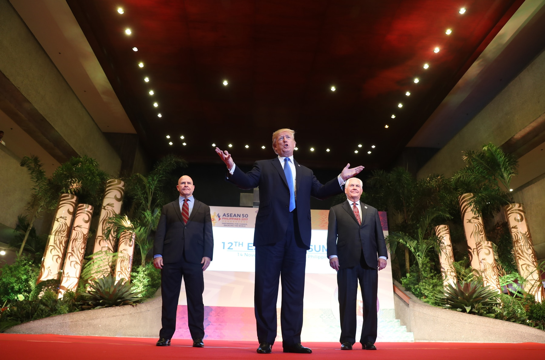 Three men standing on a stage (© AP Images)