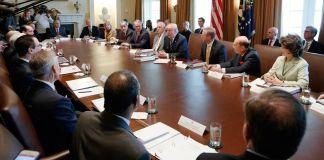 Muitas pessoas sentadas ao redor da mesa longa (© AP Images)