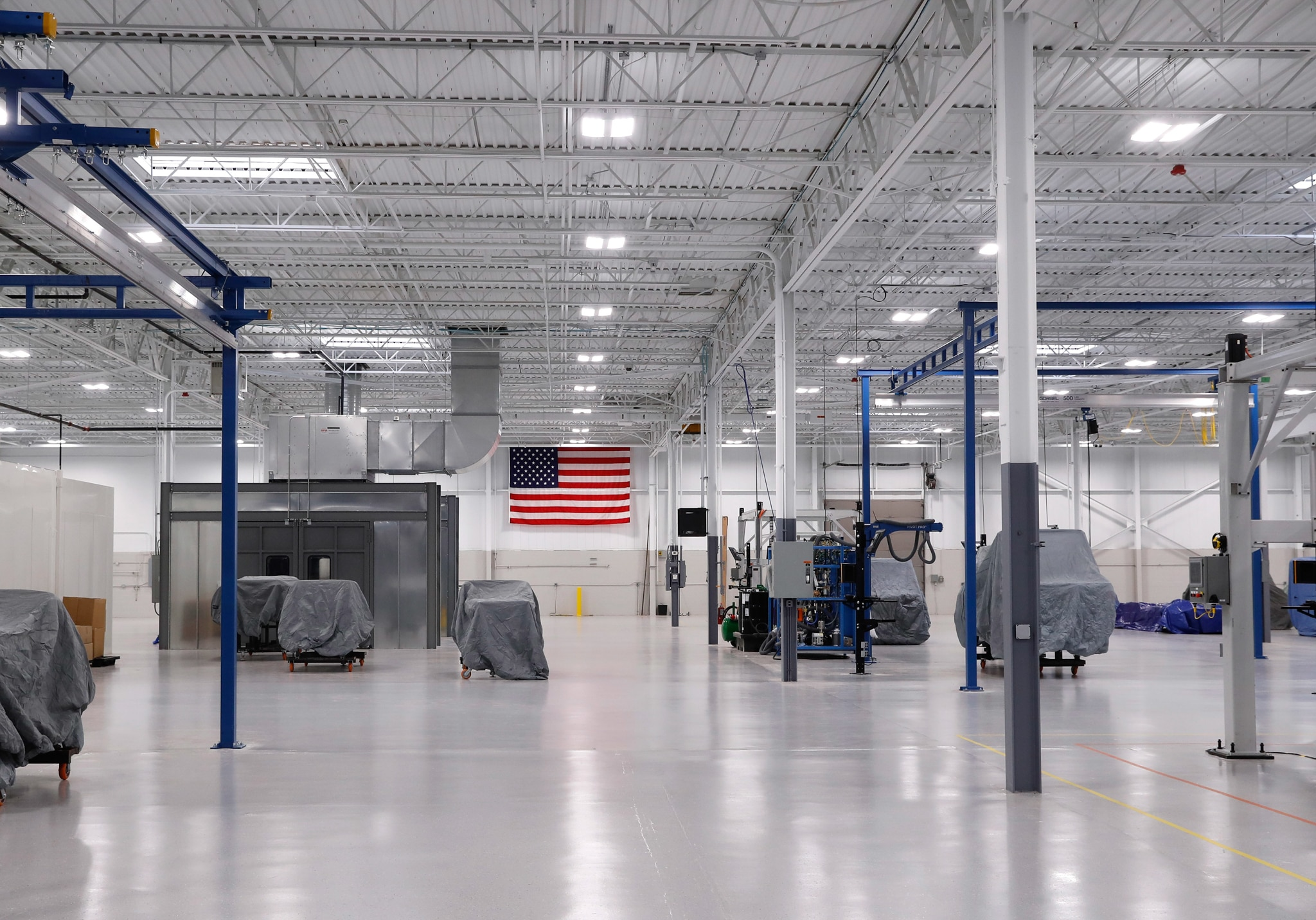 Spacious plant floor with covered machinery and American flag on back wall (© AP Images)