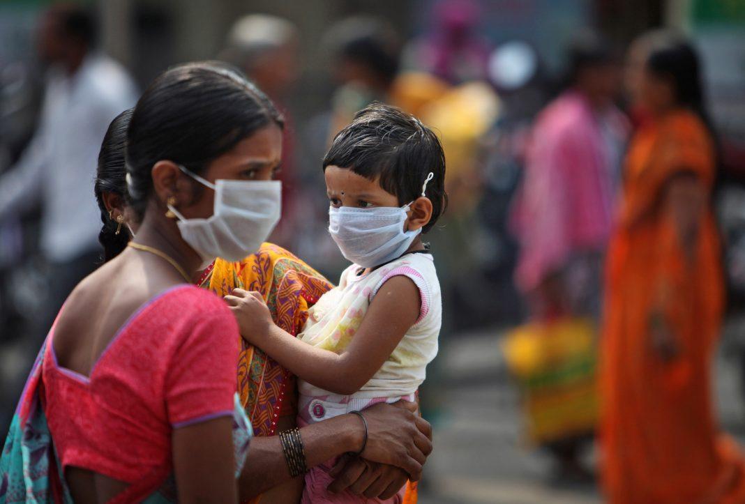 Mulher e criança usam máscaras no rosto (© AP Images)