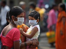 Woman and child wearing face masks (© AP Images)