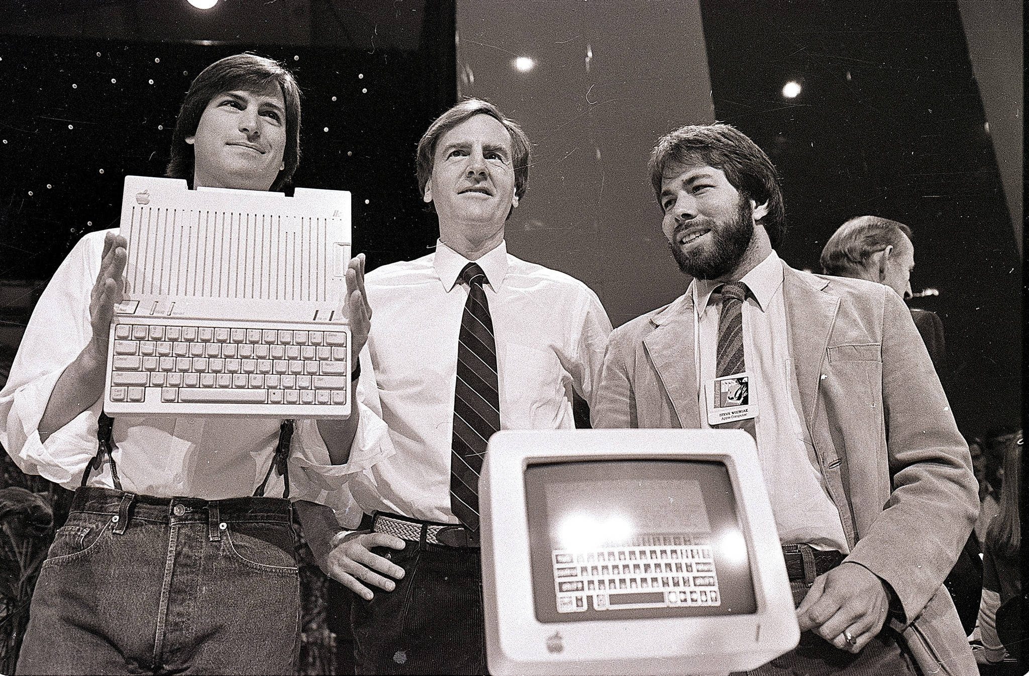Three men standing behind a computer, one holding a keyboard (© AP Images)