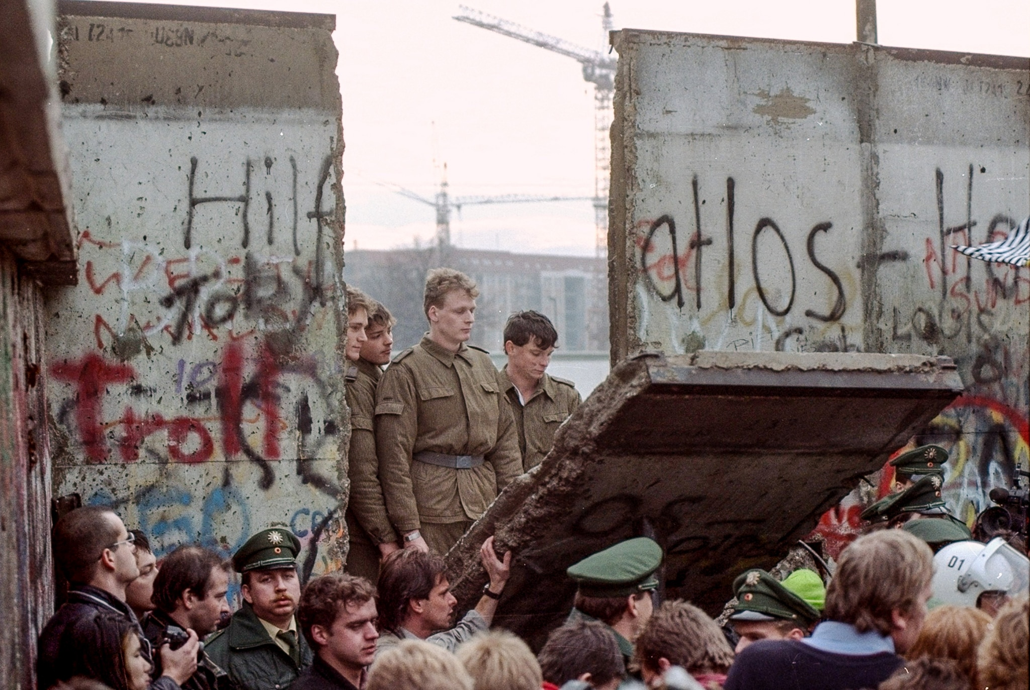 Soldiers and other people standing around opening in concrete wall (© AP Images)