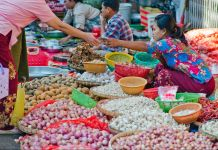 Vendor surrounded by bowls of food items in street (© Alamy)