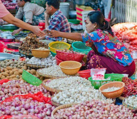 Pasar pinggir jalan yang ramai di Yangoon, Myanmar. Wanita pengusaha asal Haiti-Amerika, Christine Souffrant Ntim, menyusun daftar situs tentang pedagang kaki lima di kota-kota besar untuk wisatawan. (© Alamy)