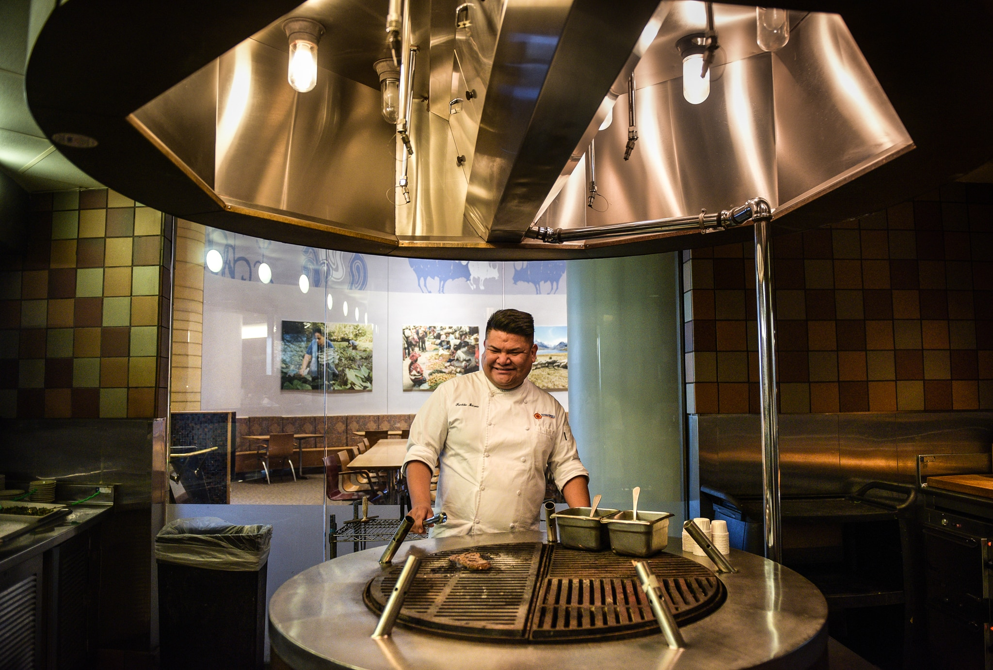 Freddie Bitsoie cooking meat on grill in large kitchen (© Carol Guzy)