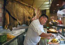 Hombre preparando comida en un plato en un mostrador de alimentos, con una piel de búfalo colgada detrás suyo en la pared (© Carol Guzy)