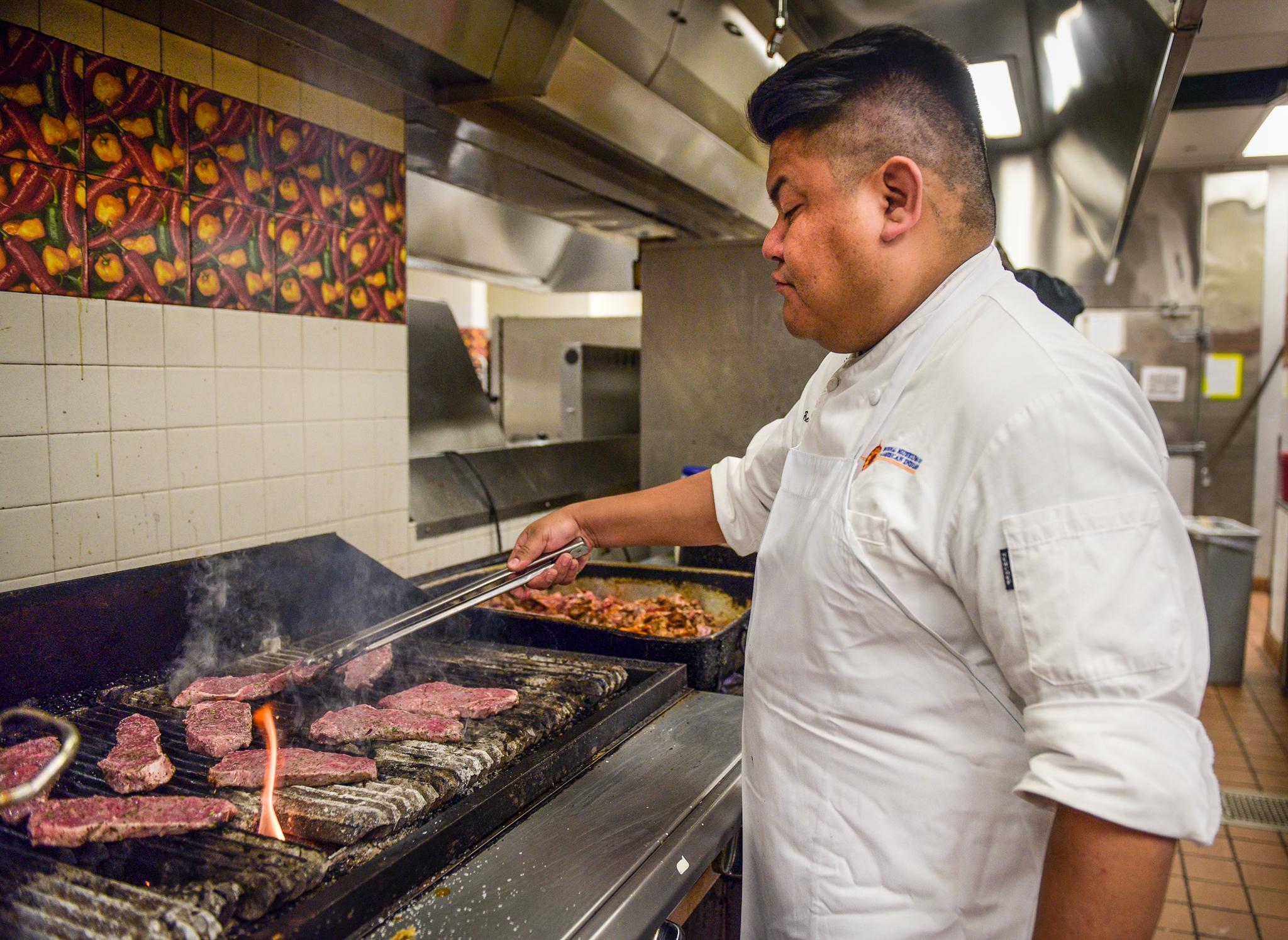 Hombre manipulando un pedazo de carne en una plancha grande con largas tenazas (© Carol Guzy)