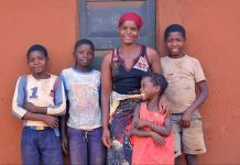 Woman standing against wall with four children (© Sarah Day Smith/PEPFAR)