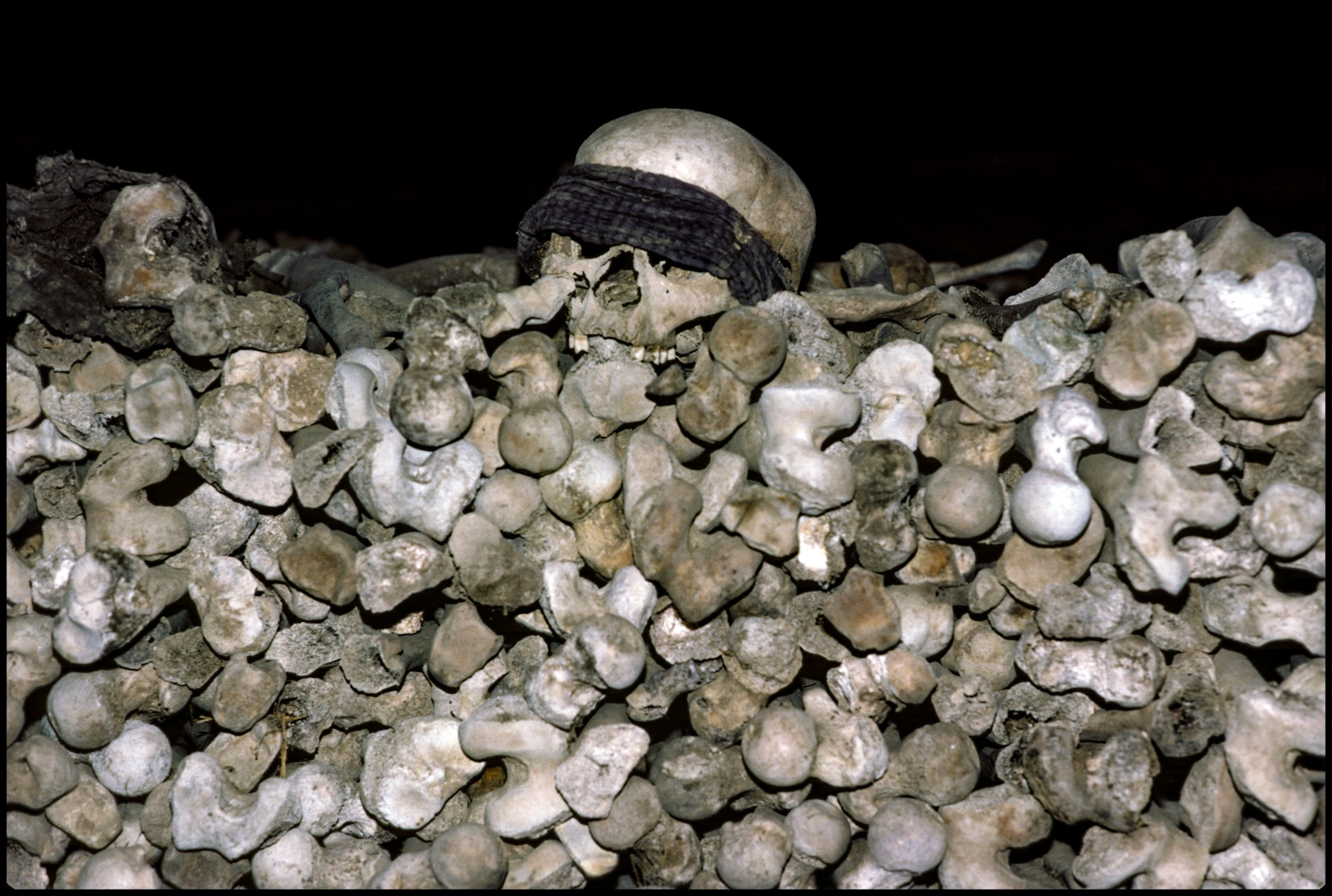 Large pile of bones with blindfolded skull on top (© Alex Bowie/Getty Images)