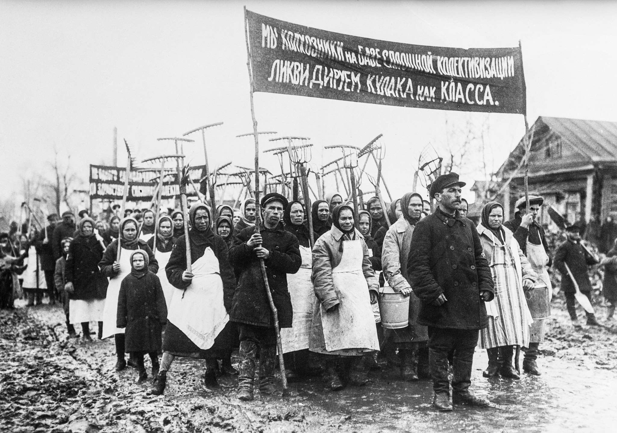 Men, women and children in rude clothing marching as group, holding farm implements and banner (© Bettmann/Getty)