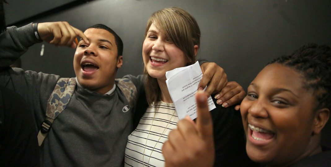 Two students congratulating teacher (© Pat Greenhouse/Boston Globe/Getty Images)