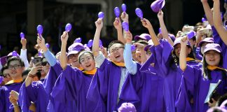 Students in purple graduation robes cheering (© Dia Dipasupil/Getty Images)