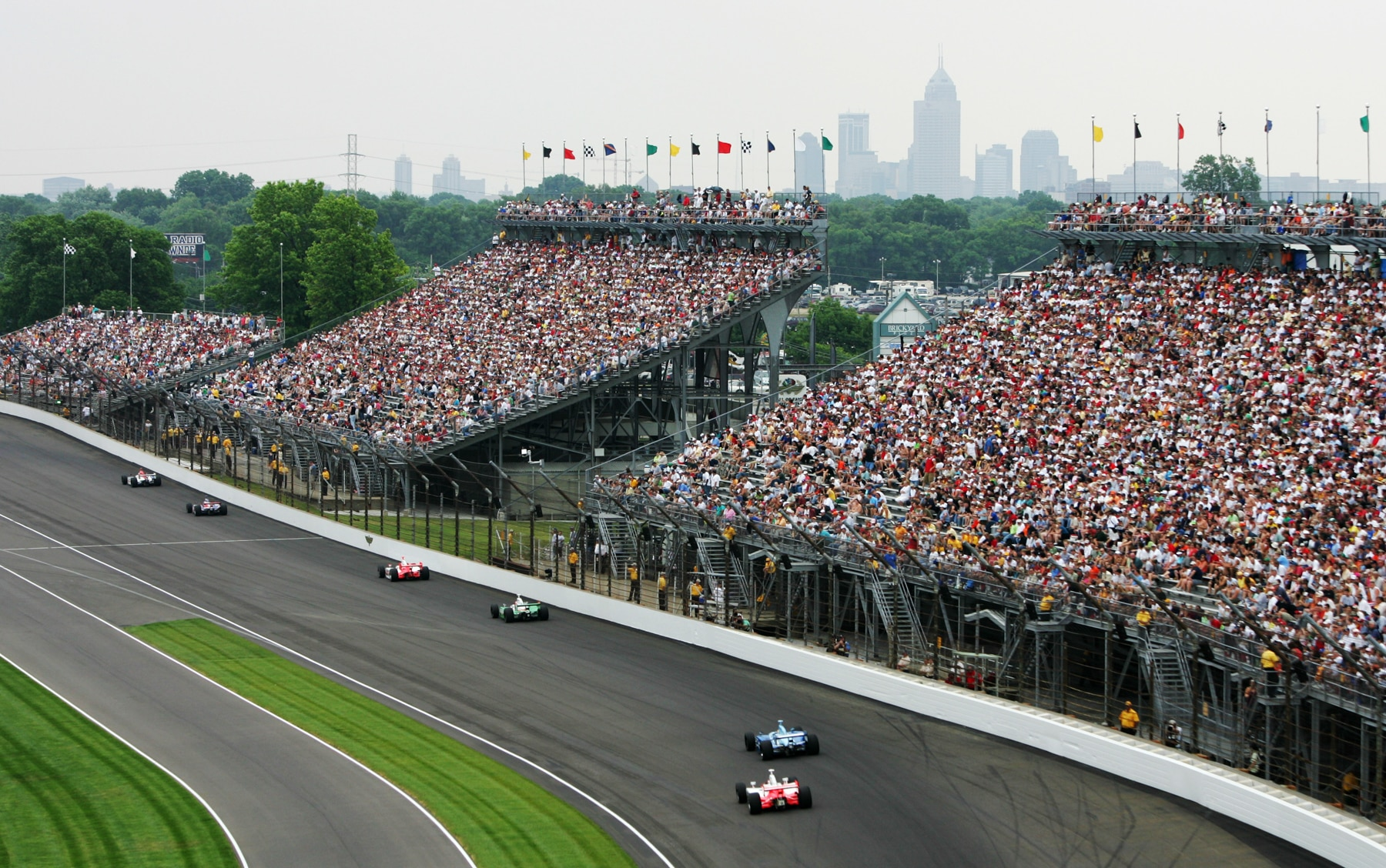 Cars racing on racetrack, large crowd in stands (© Robert Laberge/Getty Images)