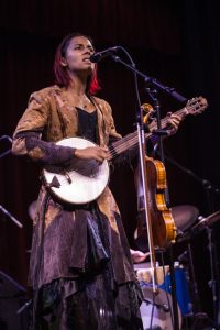 Woman onstage singing and playing a banjo (© Jeff Hahne/Getty Images)