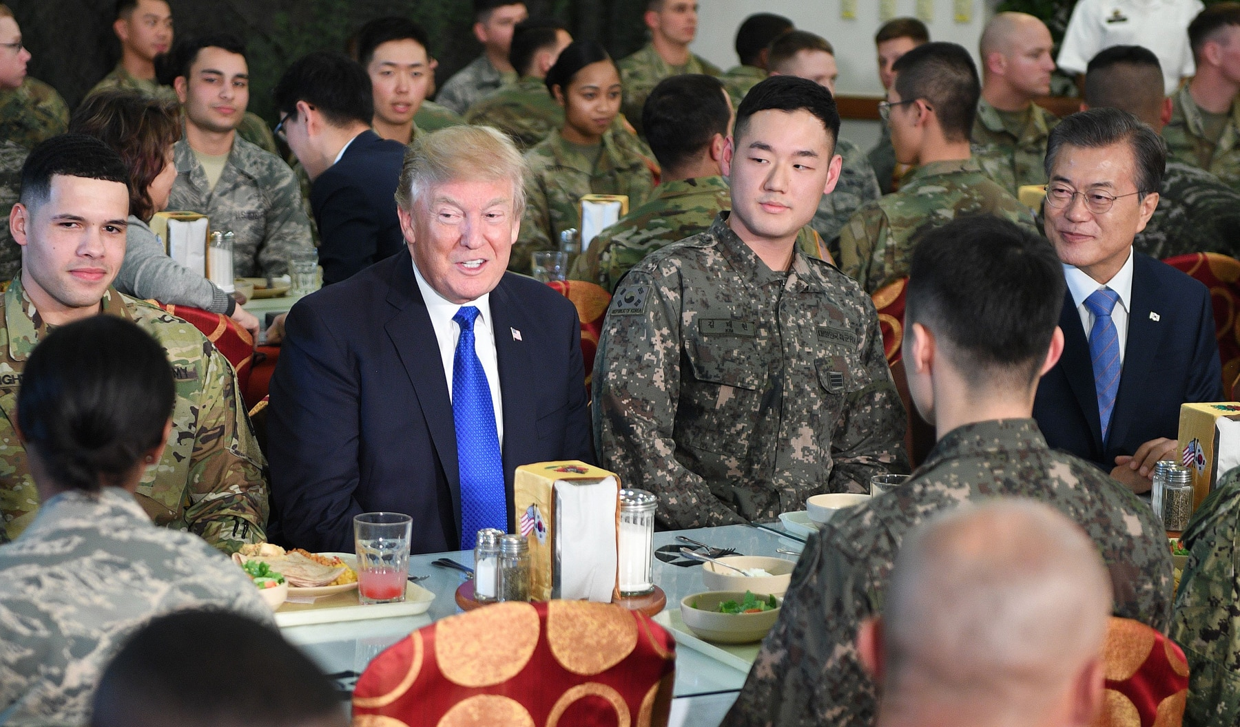 U.S. President Donald Trump and South Korean President Moon Jae-in sitting with military personnel (© Jim Watson/AFP/Getty Images)