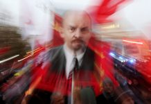 Blurred photo of rally, with poster of Lenin surrounded by red color (© Valery Sharifulin/TASS/Getty Images)