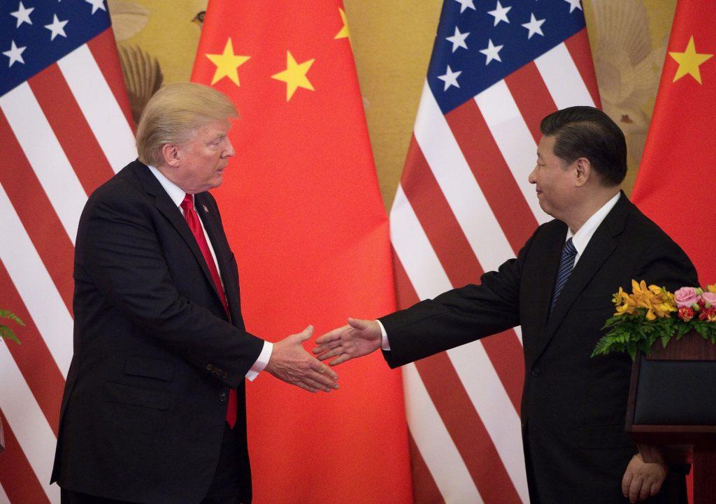 국기 앞에서 악수하는 트럼프 대통령과 시진핑 국가주석 (© Nicolas Asfouri/AFP/게티 이미지)