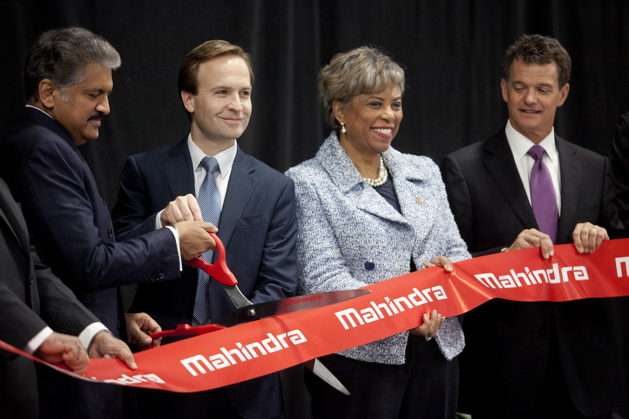 Three people holding large ribbon as two cut it with huge scissors (© Laura McDermott/Bloomberg/Getty Images)