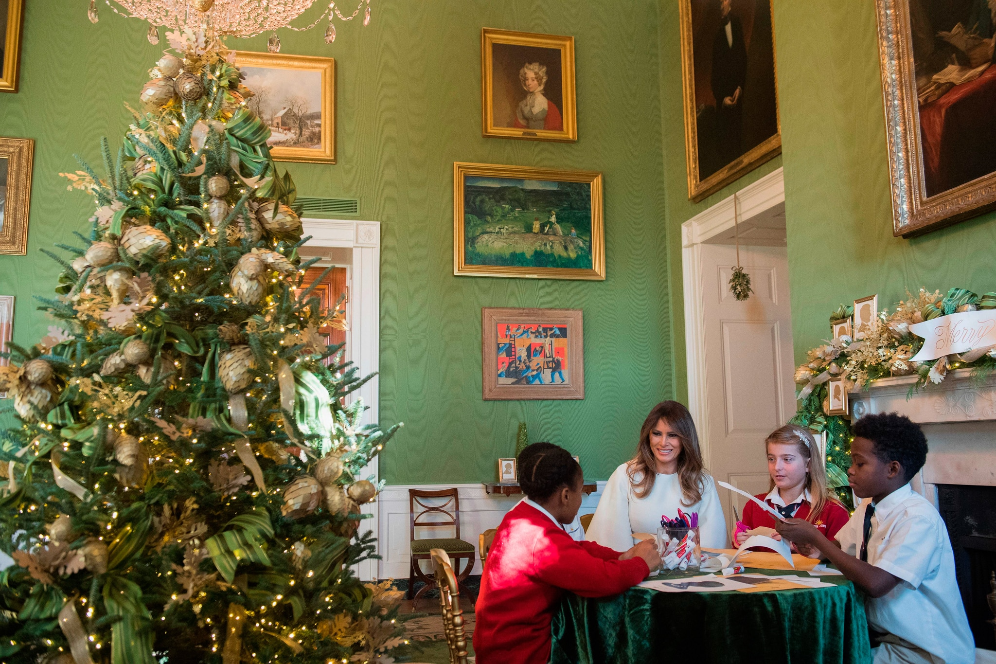 Christmas tree in a green room where four people are sitting at a table (© Saul Loeb/AFP/Getty Images)
