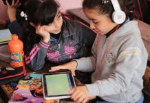 Two girls listening to a tablet through headphones (USAID)