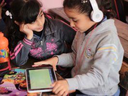 Duas meninas com fones de ouvido praticam a compreensão oral com a ajuda de um tablet (Usaid)