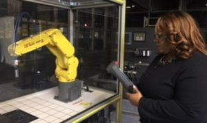 Woman holding instrument in front of case with robotic arm in it (Courtesy of Rochelle White)