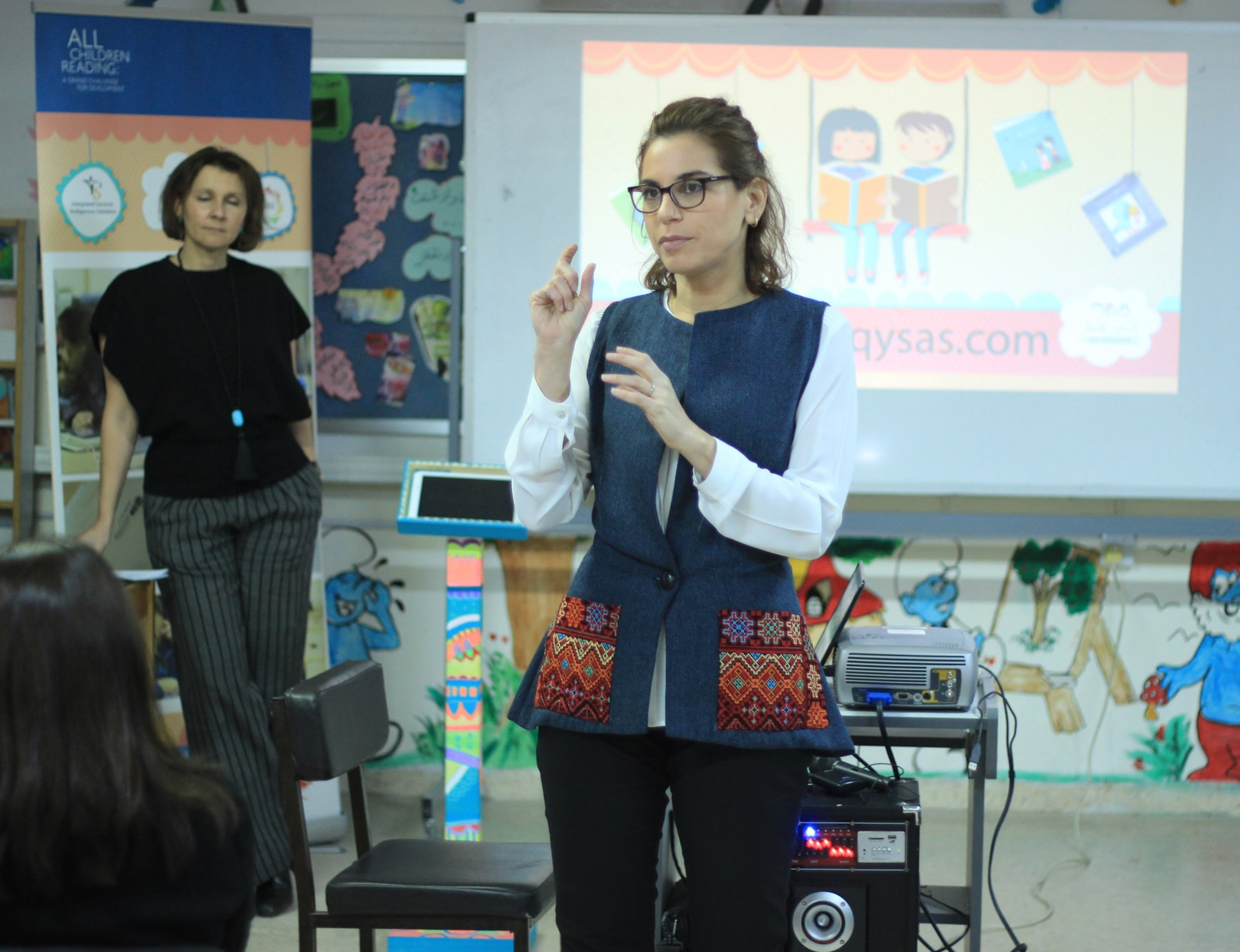 Woman speaking in front of a classroom (USAID)