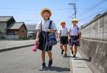 Three young schoolchildren walking on road (© QxQ Images/Alamy)