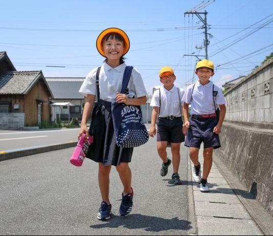Three young schoolchildren walking on road (© QxQ Images/Alamy)