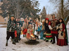 Group of costumed people standing in snow around fire (© Erika Larsen/National Geographic Creative)