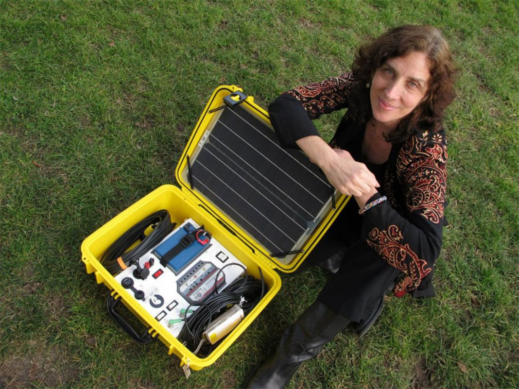 Woman squatting next to open solar suitcase (Courtesy of Laura Stachel)