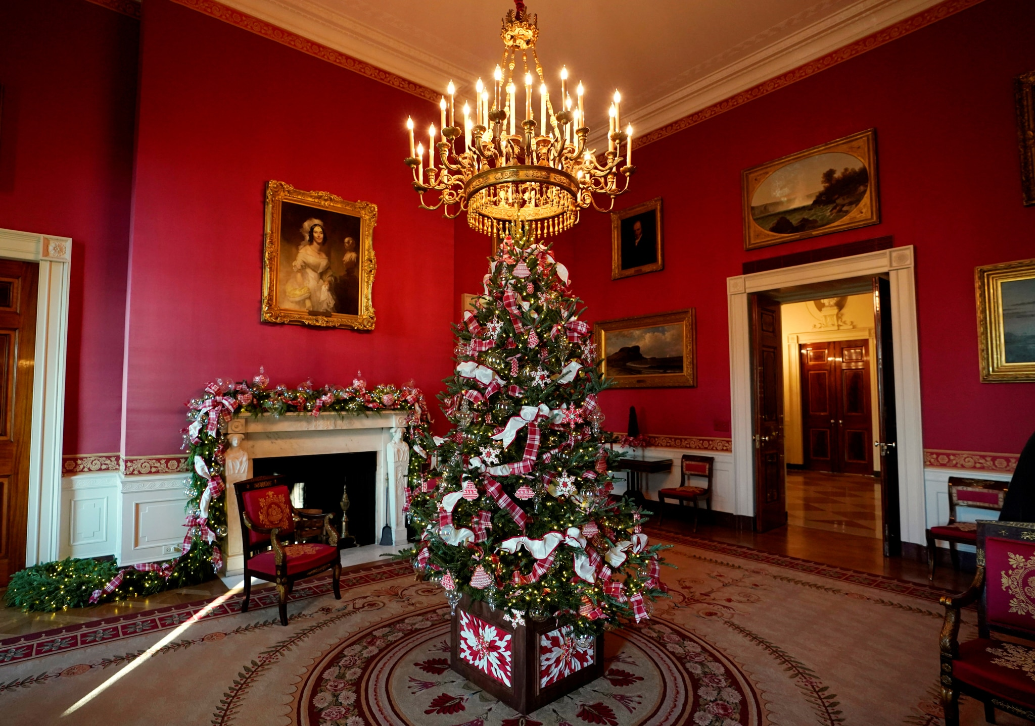 Red room with Christmas tree under chandelier (© Kevin Lamarque/Reuters)