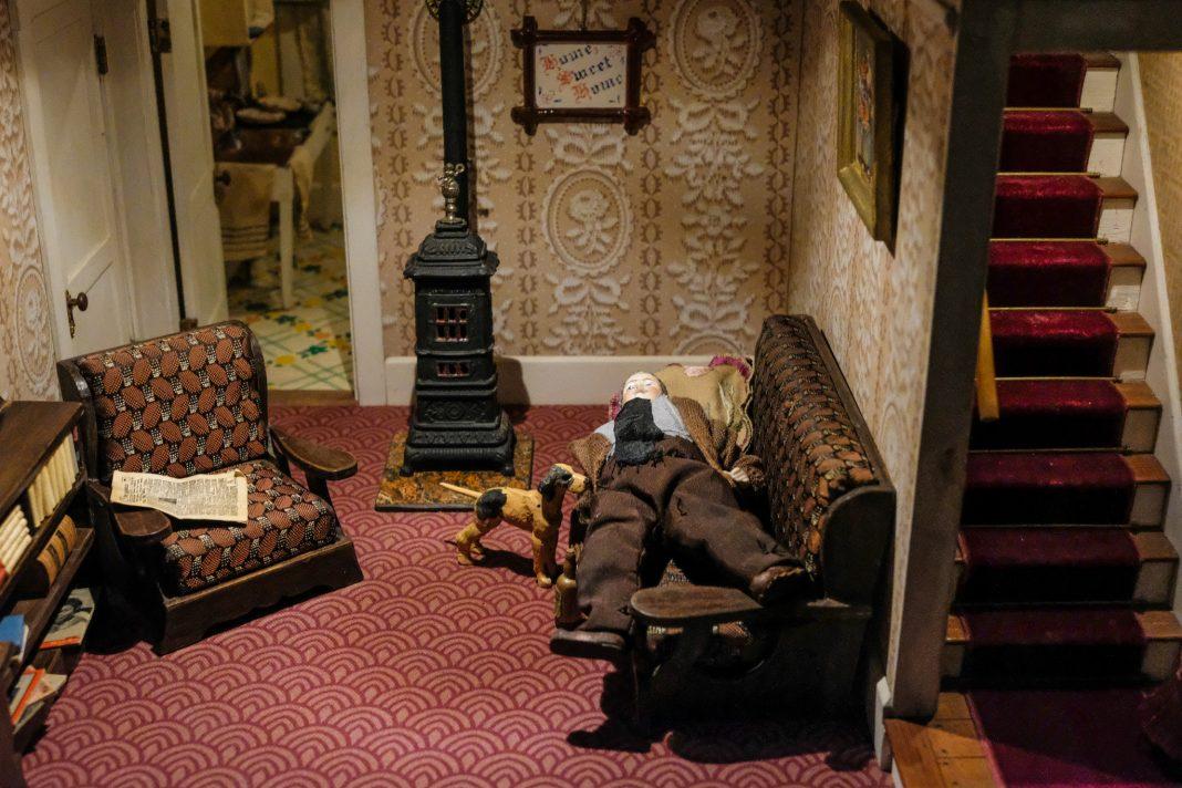 Scène miniature d'un chien regardant un homme allongé sur un canapé dans un salon (Département d'État/S. L. Brukbacher)