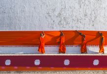 Four monks in orange robes hanging orange drape on temple (© Stanley J. Staniski/Smithsonian Institution)