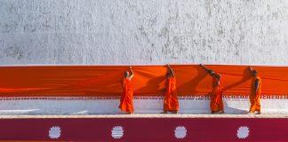 Cuatro monjes con túnicas anaranjadas colocan telas anaranjadas en un templo (© Stanley J. Staniski/Instituto Smithsoniano)