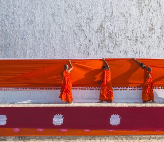 Four monks in orange robes hanging orange drape on temple (© Stanley J. Staniski/Smithsonian Institution)