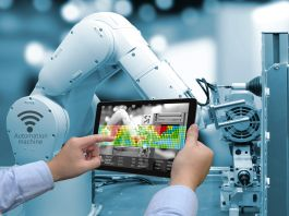 Man holding tablet in front of robotic arm (Shutterstock)