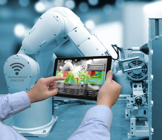 Homem segura tablet na frente de braço robótico (Shutterstock)