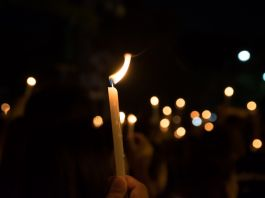 Hand holding lit candle (Shutterstock)
