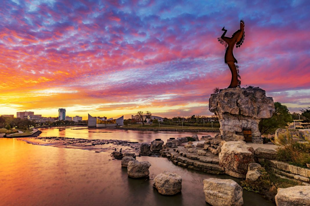 Sculpture on river bank, city skyline in background (© Shutterstock)