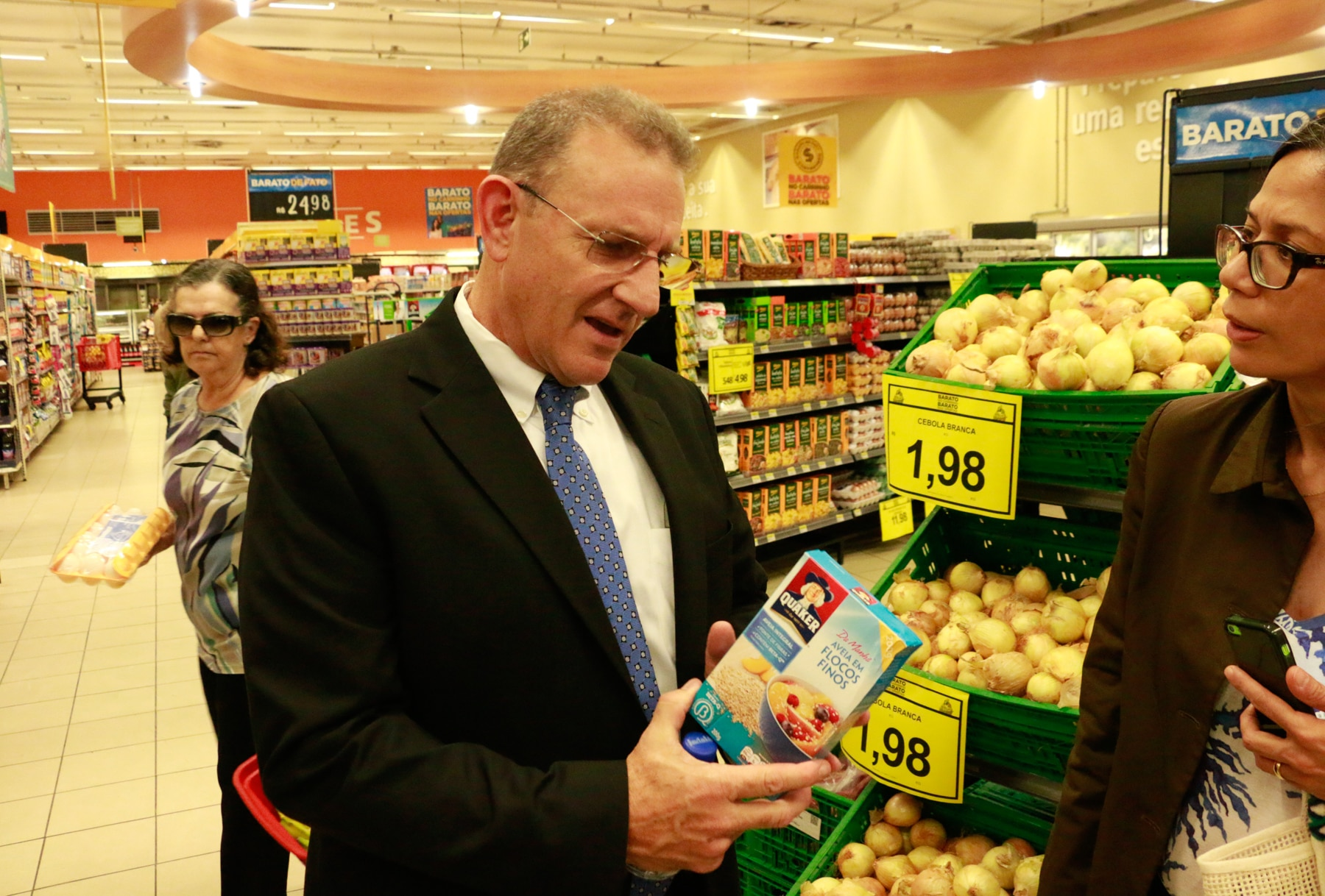 Man wearing business suit holding product in grocery store (USDA)