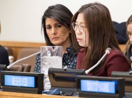 Woman speaking into microphone as another looks on (United Nations)