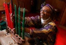Mujer con tocado en la cabeza y una blusa floreada colocando velas en un candelabro (© AP Images)
