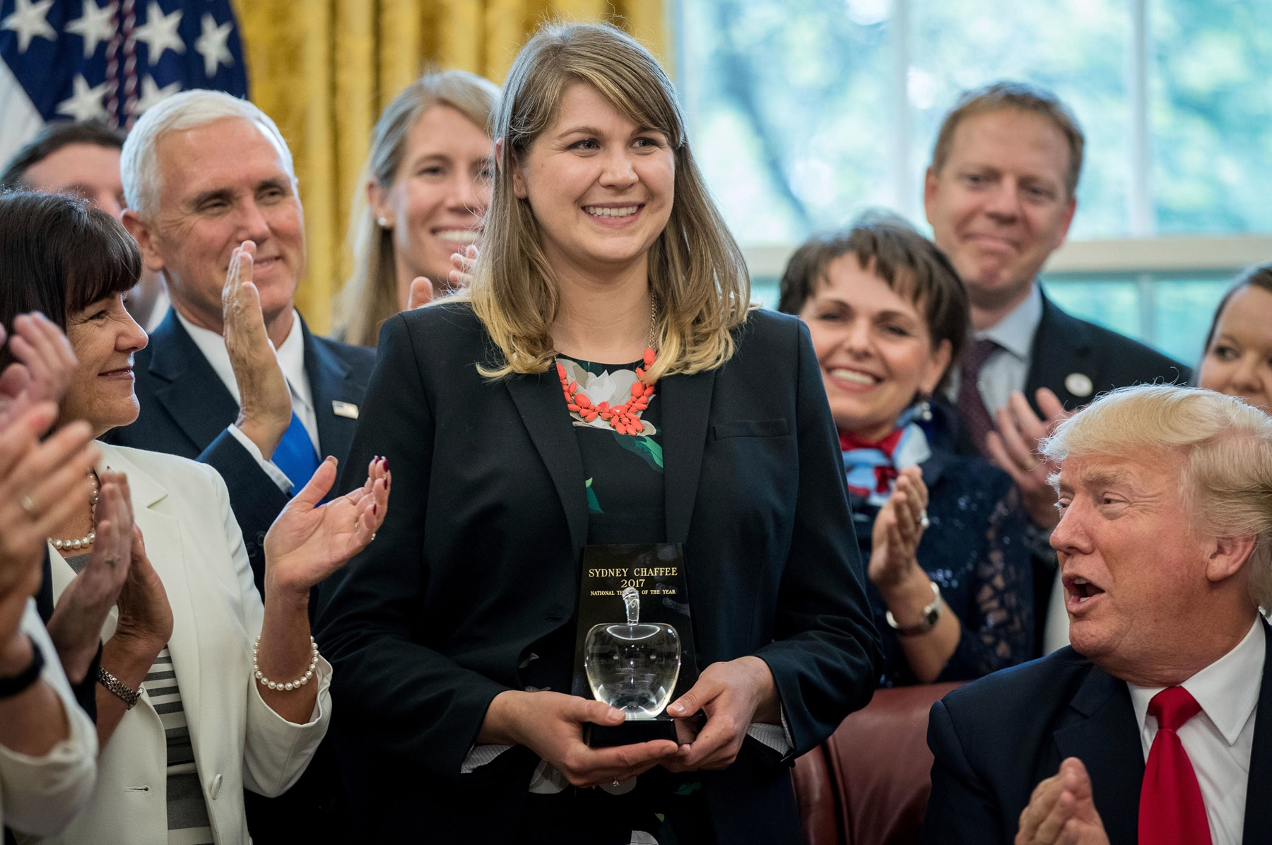 Woman holding award with people surrounding her applauding (© AP Images)