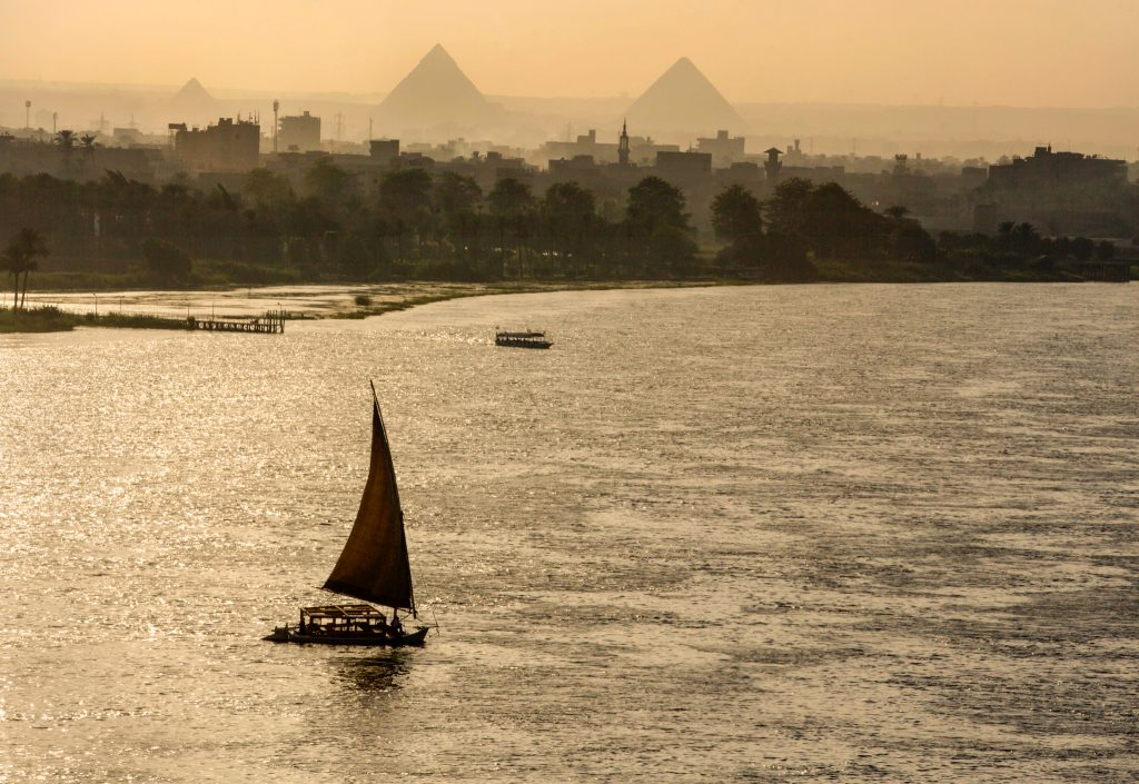 Sailboat on river, pyramids in distance (© AP Images)