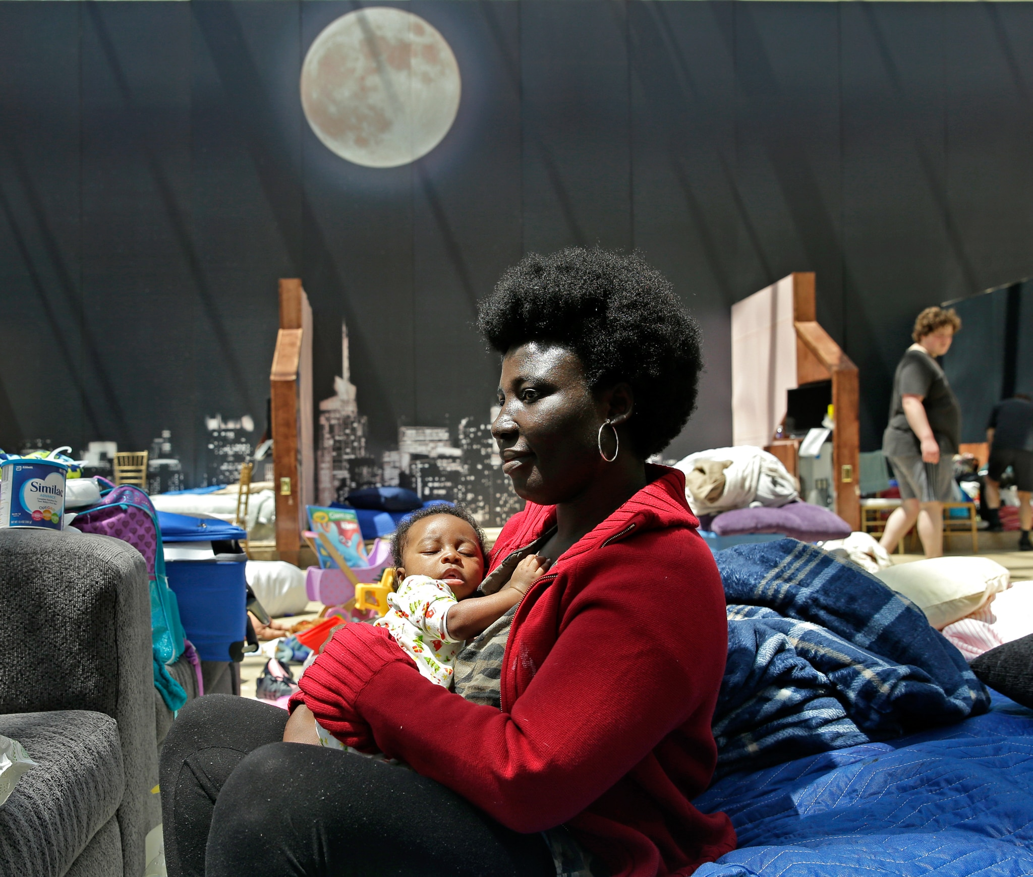 Woman holding baby with moon and cityscape painted on wall behind her (© AP Images)